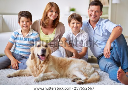 Portrait of two brothers, their parents and dog sitting on the floor - stock photo