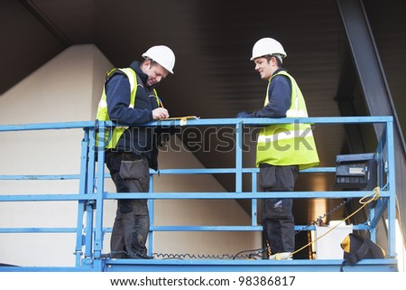 Portrait of two builders standing on platform at building site. The foreman is signing papers. - stock photo