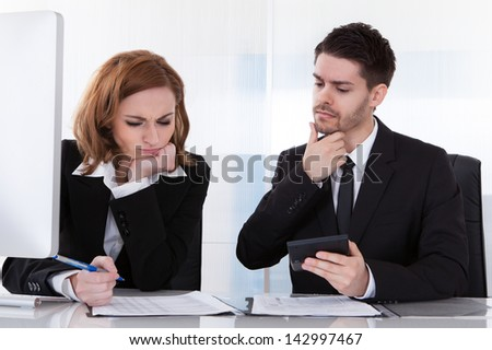 Portrait of two business colleagues at office working together - stock photo