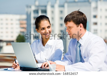 Portrait of two business partners working outside on background of houses - stock photo