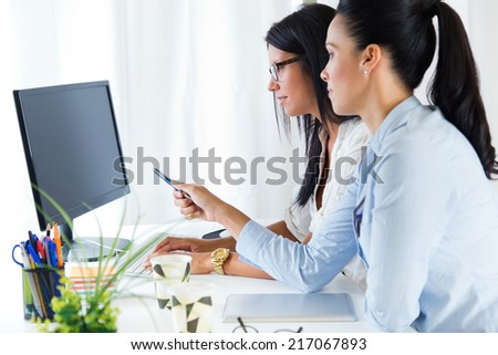Portrait of two business woman working in office with computer. - stock photo