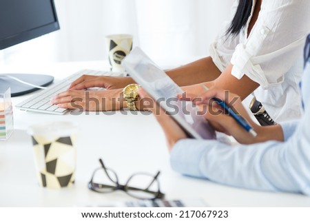 Portrait of two business woman working in office with digital tablet. - stock photo