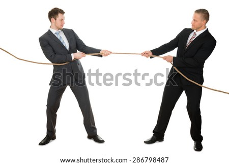 Portrait Of Two Businessman Pulling Rope Over White Background - stock photo