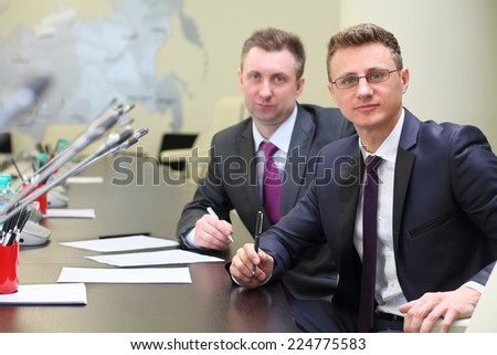 Portrait of two businessmen at negotiating table in conference hall - stock photo