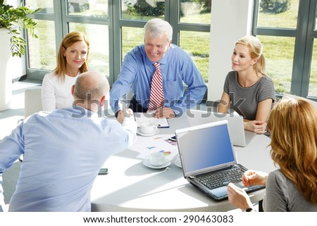 Portrait of two businessmen shaking hands while making agreement and sitting at business meeting. Business people using laptop and digital tablet while sitting around conference table.  - stock photo