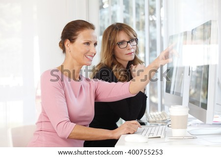 Portrait of two businesswomen sitting at office and working together on computer on new project.  - stock photo