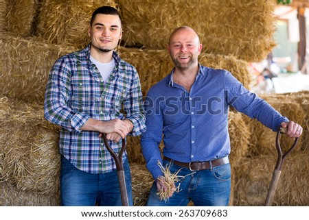 Portrait of two casually clothed farmers with holding pitchforks in a barn near haystack - stock photo