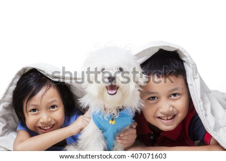 Portrait of two cheerful children having fun with a maltese dog under blanket, isolated on white background - stock photo
