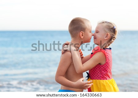portrait of two children kissing on the beach - stock photo