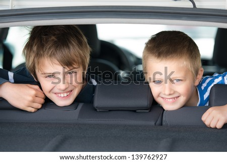 Portrait of two children smiling inside the car - stock photo