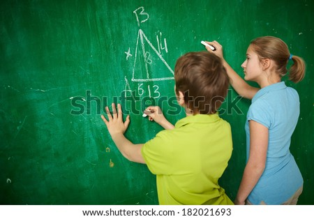 Portrait of two classmates by the blackboard at the lesson of geometry - stock photo