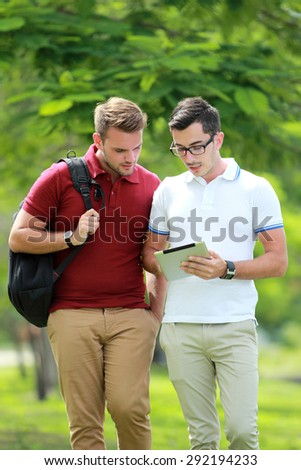 portrait of two college students discussing a subject while walking at college park - stock photo