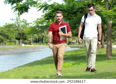 portrait of two college students walking together at riverside - stock photo