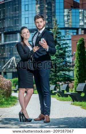 Portrait of two confident and successful businessmen. Business couple standing embracing and holding mobile phone. - stock photo
