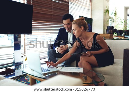 Portrait of two confident business partners discussing ideas on net-book during meeting, successful woman reveals something  for her male colleague using laptop computer and touch pad for teamwork - stock photo