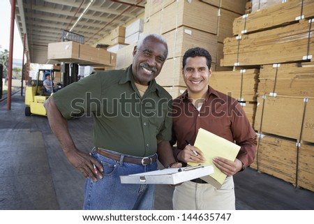 Portrait of two confident workers and man working with forklift in background - stock photo