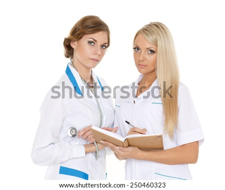 Portrait of two confident young female doctors standing on a white background. - stock photo