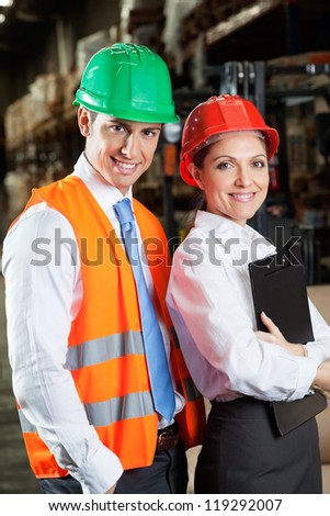 Portrait of two confident young supervisors standing at warehouse - stock photo