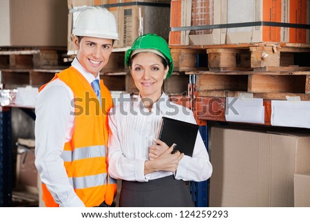 Portrait of two confident young supervisors with book standing at warehouse - stock photo