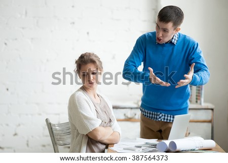 Portrait of two coworkers arguing at work. Staff in the middle of argument at modern office. Young furious man yelling at annoyed stressed woman with crossed arms. Negative human emotions - stock photo