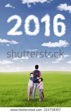 Portrait of two cute children embrace their father on the meadow under numbers 2016. New year concept - stock photo