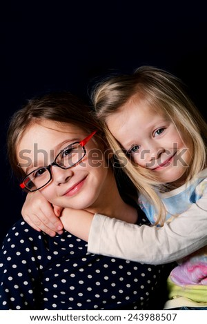 Portrait of two cute girlfriends or sisters, vertical studio shot with blue background - stock photo