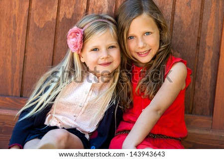 Portrait of two cute girlfriends sitting next to wooden wall. - stock photo