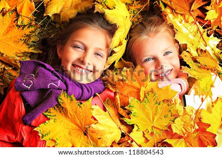 Portrait of two cute girls sisters lying on the leaves at the autumn park. - stock photo