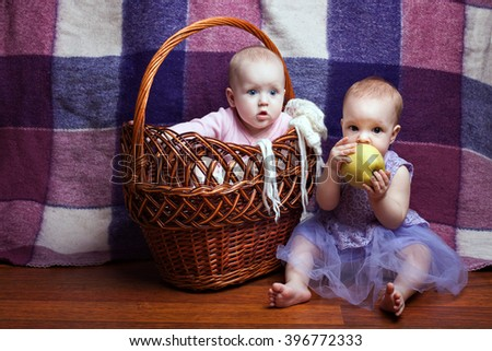 Portrait of two cute little girls. One girl sitting in a basket, the second girl sitting beside her and gnawed apple - stock photo