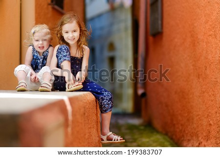 Portrait of two cute little sisters at summer - stock photo