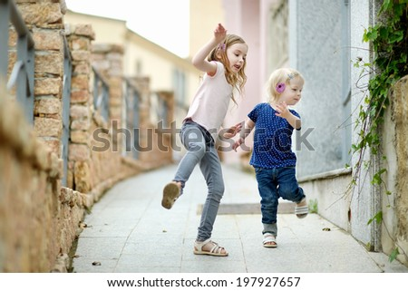 Portrait of two cute little sisters outdoors - stock photo