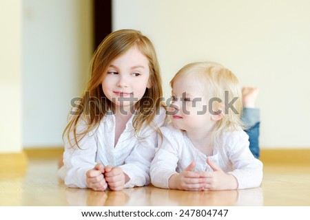 Portrait of two cute sisters at home - stock photo