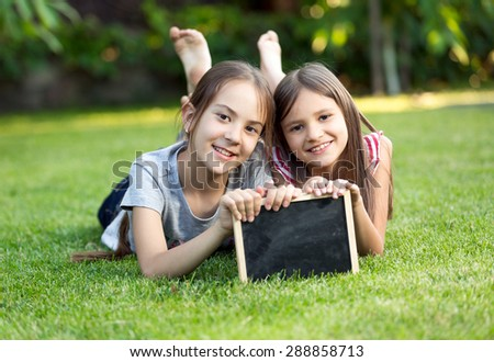 Portrait of two cute smiling girls lying on grass with chalkboard - stock photo