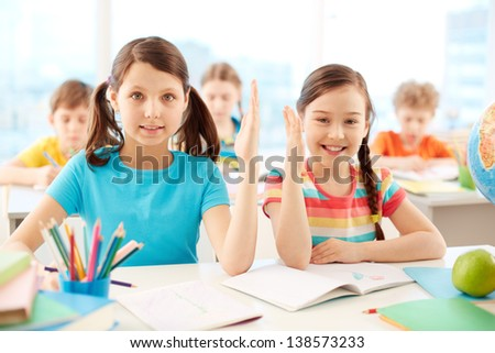 Portrait of two diligent girls raising hands at workplace with classmates on background - stock photo