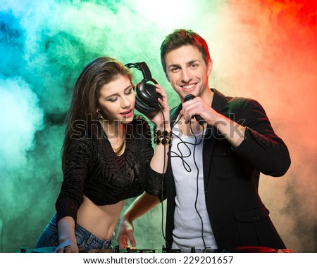 Portrait of two DJ's at the work, in the club. Light and fog on the background. - stock photo
