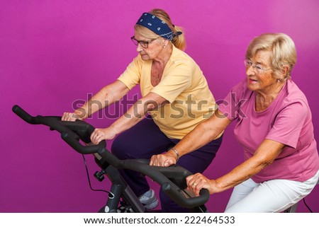 Portrait of two Elderly women doing leg exercises on stationary bikes in gym. - stock photo