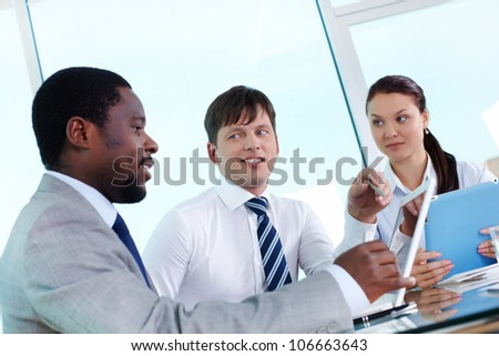 Portrait of two employees listening to explanation of their colleague at meeting - stock photo