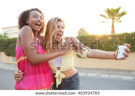Portrait of two ethnically diverse teenager girls posing together laughing while using a smart phone to take selfies on sunset suburban street, outdoors lifestyle. Young people using technology. - stock photo
