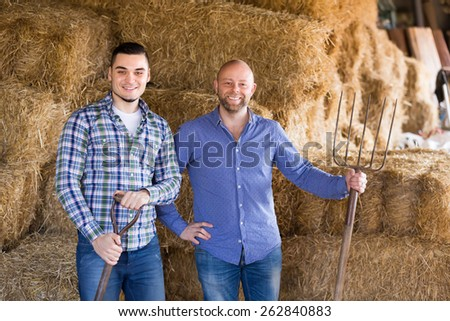 Portrait of two farmers with working tools in barn - stock photo