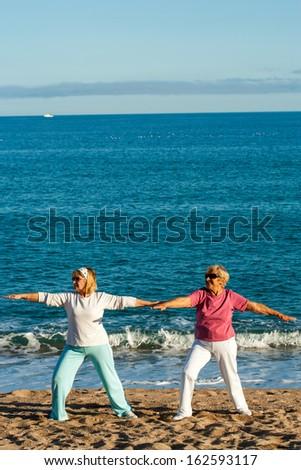 Portrait of two female elderly ladies doing yoga on beach. - stock photo