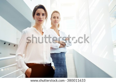 Portrait of two female financiers with satisfied faces are concept of guarantees reliability and performance, team of confident women leaders posing in modern office interior, copy space for content - stock photo
