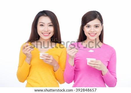 Portrait of two friendly asian woman friends eating yoghurt promoting healthy lifestyle and dieting. - stock photo