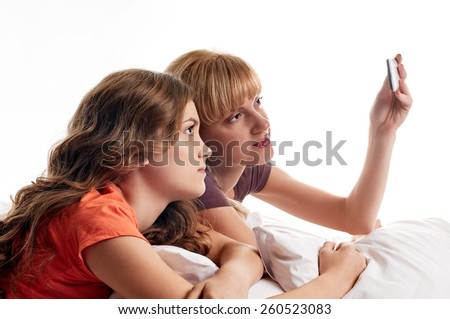 portrait of two friends sisters taking photos with a smartphone. profile faces - stock photo