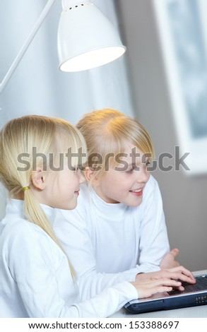 Portrait of two girls doing homework at computer    - stock photo