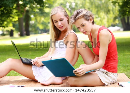 Portrait of two girls hanging out at a park while using their laptops - stock photo