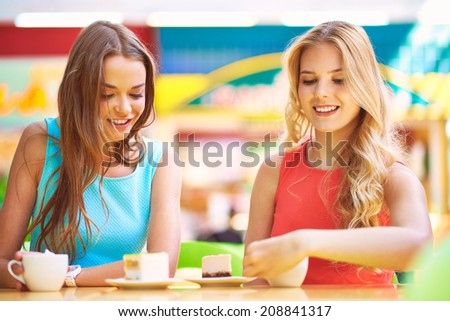 Portrait of two girls having cheesecakes with coffee - stock photo
