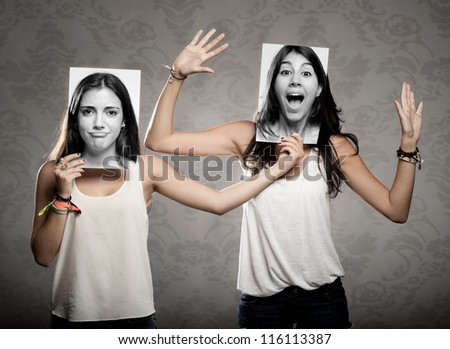 portrait of two girls holding a photography in front of face - stock photo