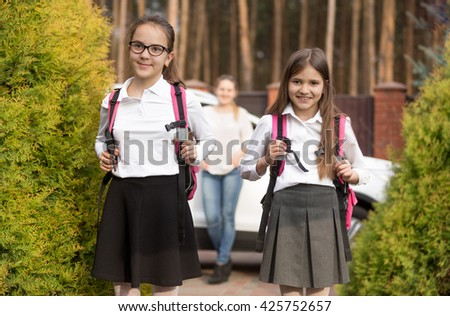 Portrait of two girls posing with school bags after lesson in school - stock photo