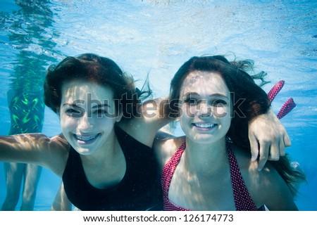 Portrait of two girls swimming underwater - stock photo