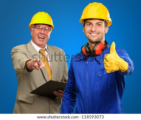 Portrait Of Two Happy Architect Engineers While Gesturing On Blue Background - stock photo